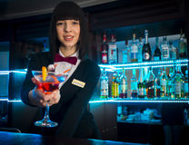 Bartender girl at night club counter offering coctail b Stock Photography