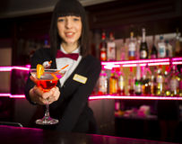 Bartender girl at night club counter offering coctail barmaid Royalty Free Stock Photos