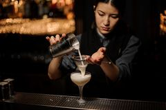 Bartender girl pouring a delicious cocktail from the steel shaker through the sieve. To a glass on the bar counter on the blurred background stock photography