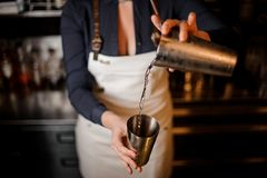 Bartender girl pourring an alcoholic drink from one steel cup to another royalty free stock photos