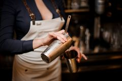 Bartender girl pourring a cocktail drink from one steel cup to another royalty free stock image