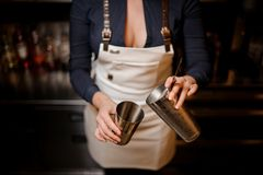 Bartender girl pourring a cocktail from one steel cup to another stock images