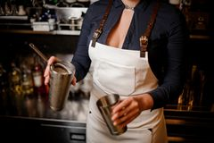 Bartender girl holding steel cocktail shaker with drink. Bartender girl in the white apron holding in her hands steel cocktail shaker at the bar counter stock photography
