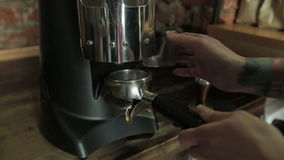 Bartender grinding coffee for espresso in stock footage