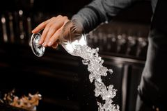 Bartender hand pouring a full cocktail glass with ice. Cocktail on the background of bar counter Stock Photos