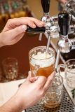 Bartender hands pouring a draught craft beer into a mug royalty free stock image