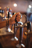 Bartender hands using beer tap in pub Stock Photography