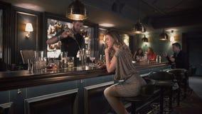 Bartender Hipster που συνδυάζει τα συστατικά και που κατασκευάζει τα κοκτέιλ στο φραγμό ενώ η νέα όμορφη γυναίκα κάθεται κοντά στ απόθεμα βίντεο