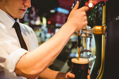 Bartender holding beer glass below dispenser tap Royalty Free Stock Photos