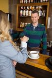 Bartender Holding Card-Reader While Woman Making Stock Photography