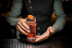 Bartender holding a glass with fresh summer light sour cocktail with pink peach liquor decorated with flower. Barman hand holding a glass with fresh summer light Stock Image