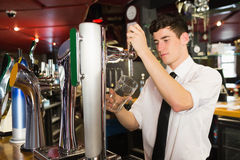 Bartender holding glass standing in front of dispenser Royalty Free Stock Image