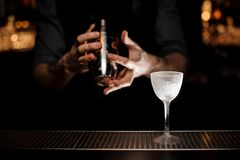Bartender holding a steel shaker on the foreground of glass. On the bar counter in the dark blurred background royalty free stock images