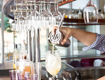 Bartender holding steel shaker up and pouring mixed drink into t. Bartender behind the bar counter is holding steel shaker up and pouring mixed drink into the stock photos