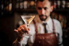 Bartender holding a transparent cocktail in the martini glass. Bartender in the white shirt and brown leather apron holding a transparent cocktail in the martini stock image