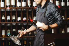 Bartender holds bottle of wine and unusual glass vessel stock images