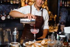 Bartender i coctail för frukt för brunt läderförkläde en hällande alkoholiserad in i exponeringsglaset royaltyfria bilder