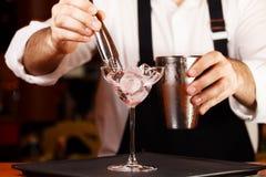 Bartender i danandecoctail på en nattklubb Tonat foto Arkivbild