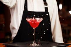 Bartender i danandecoctail på en nattklubb Tonat foto Arkivbilder