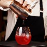 Bartender i danandecoctail på en nattklubb Tonat foto Arkivfoton
