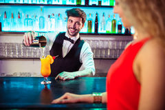 Bartender looking at woman while pouring cocktail in glass Royalty Free Stock Image