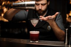 Bartender makes alcohol drink with a shaker and sieve. Brutal male bartender with beard makes red alcohol drink with a steel shaker and sieve at bar counter royalty free stock photos