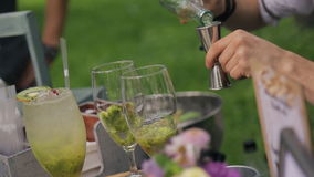Bartender makes fruity alcoholic cocktails on wedding party outdoors. Professional worker of bar using measuring cup poured into glass making drinks, adding stock video