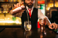 Bartender is making alcohol cocktail at counter Stock Photography