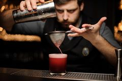 Bartender making alcohol drink using shaker and sieve. Brutal male bartender with beard making red alcohol drink using steel shaker and sieve at bar counter stock images