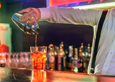 Bartender is making cocktail at bar counter. The bartender makes a cocktail at the bar, pours a glass of the shaker stock image