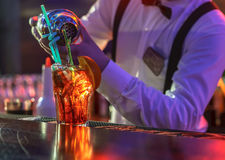 Bartender is making cocktail at bar counter. The bartender makes a cocktail at the bar, pours a glass of the shaker royalty free stock image