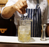 Bartender is making cocktail at bar counter, toned Stock Photos