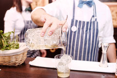 Bartender is making cocktail at bar counter, toned Stock Images