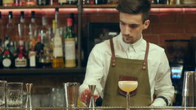 Bartender making and decorating cocktail to a visitor stock footage