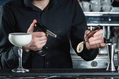 Bartender making Eggnog Cocktail garnish with a lemon chips royalty free stock photo
