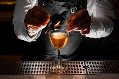 Bartender making fresh alcoholic drink with smoky note. Bartender in a white shirt making fresh alcoholic drink with smoky note on the bar counter Royalty Free Stock Images