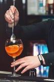 Bartender making orange margareta fresh Cocktail in bar. Bartender mixing orange  fresh Cocktail in bar with a special spoon Royalty Free Stock Photo