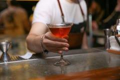 Bartender med exponeringsglas av den smakliga coctailen på räknaren i nattklubb arkivfoto