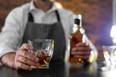 Bartender med exponeringsglas och flaskan av whisky på räknaren i stången, closeup arkivbilder