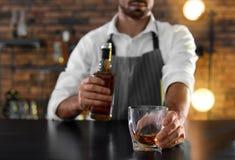 Bartender med exponeringsglas och flaskan av whisky på räknaren i stången, closeup arkivfoto