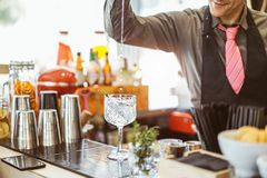 Bartender mixing a cocktail in a crystal glass in an american bar - Barman pouring alcohol in a glass with aromatic herbs stock images