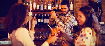 Bartender mixing a cocktail drink in cocktail shaker. At pub stock photography