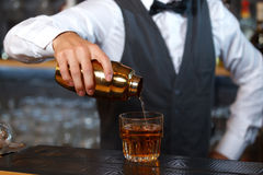 Bartender mixing drinks. Close up photo of a bartender holding a golden shaker in his hand and pouring a cocktail in a low wide glass, shelves full of bottles Royalty Free Stock Photos