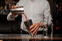 Bartender mixing in the steel cocktail shaker a transparent red alcoholic drink. On the bar counter on the blurred background royalty free stock photography