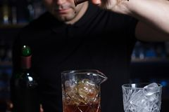 Bartender is pouring alcohol from a jigger into a measuring glass. Royalty Free Stock Images