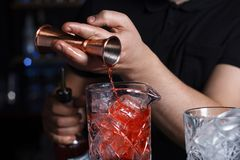 Bartender is pouring alcohol into a glass from jigger. Stock Photo