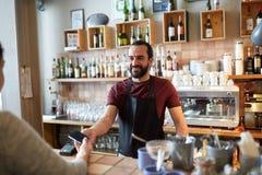 Bartender och kvinna med kortläsaren och smartphonen Arkivbild