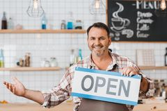 Bartender with open signboard. Happy mature bartender with open signboard at cafe royalty free stock image