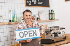 Bartender with open signboard. Smiling mature bartender with open signboard at cafe stock image