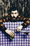 Bartender overdrink, drunk. Man in checkered shirt on wooden background, blue tablecloth. Hangover concept. Barman with beard and shocked face holds cocktail Stock Photos